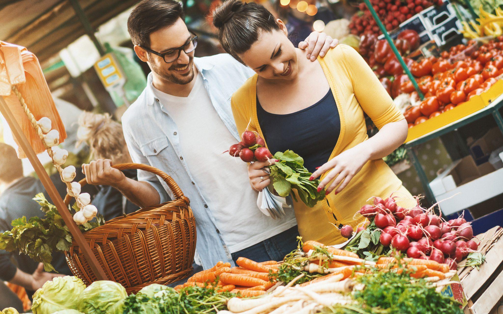 Paar das etwas Gemüse auf dem lokalen Lebensmittelmarkt wählt.