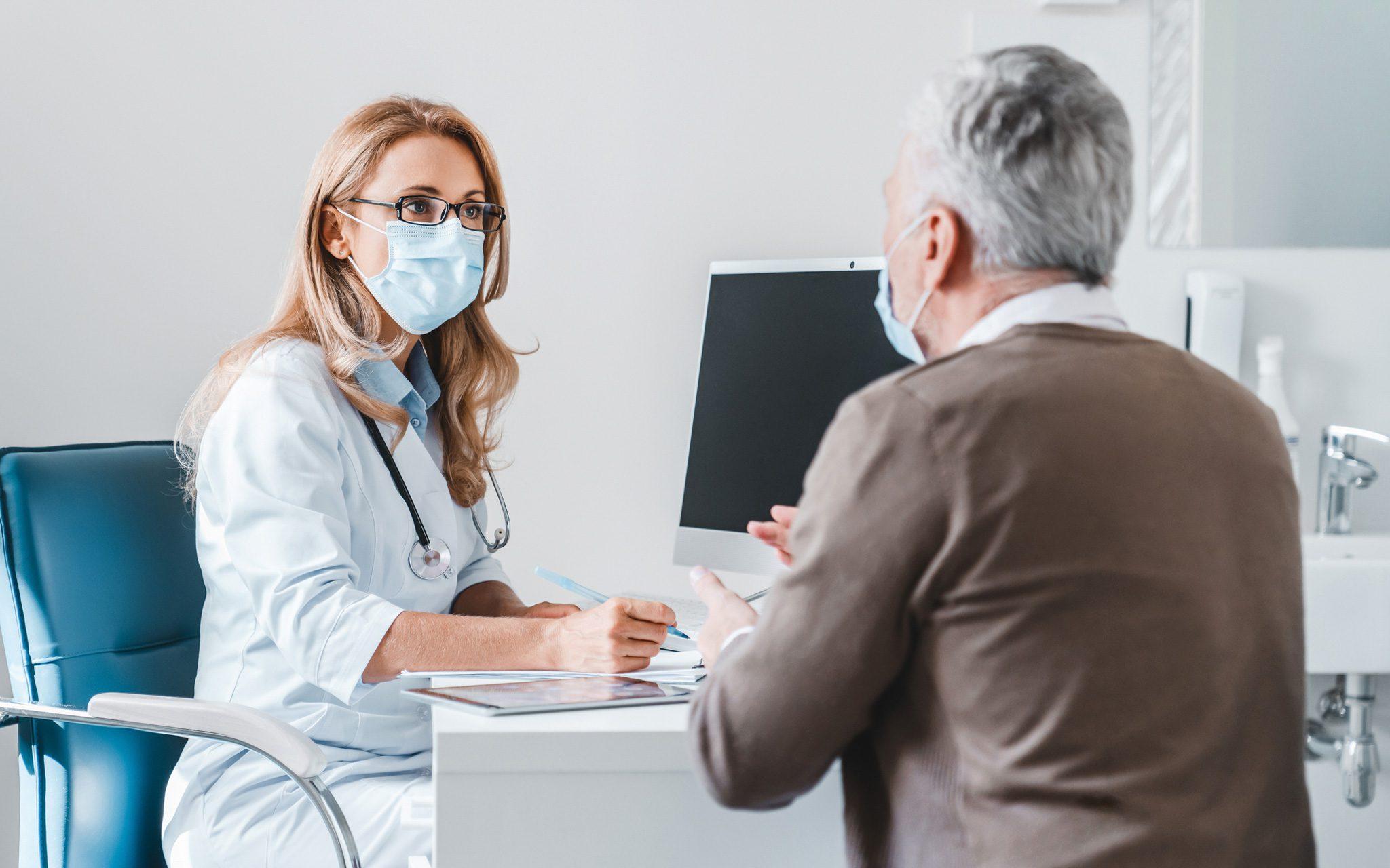 Ärztin im Gespräch mit Patienten in ihrer Praxis