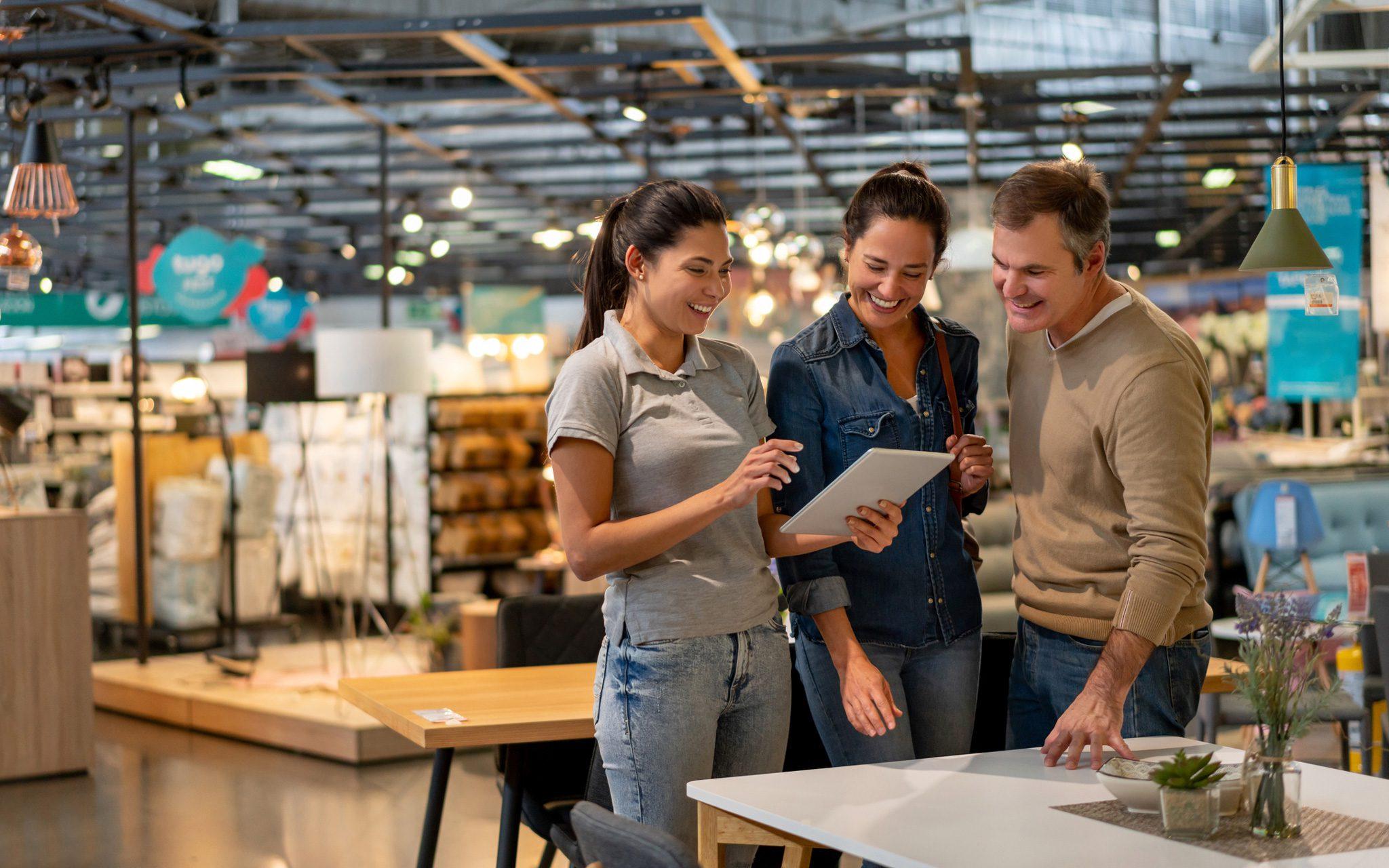 Verkäuferin, die Modelle auf einem Tablet für ein Paar zeigt, das in einem Einrichtungshaus nach Möbeln sucht.