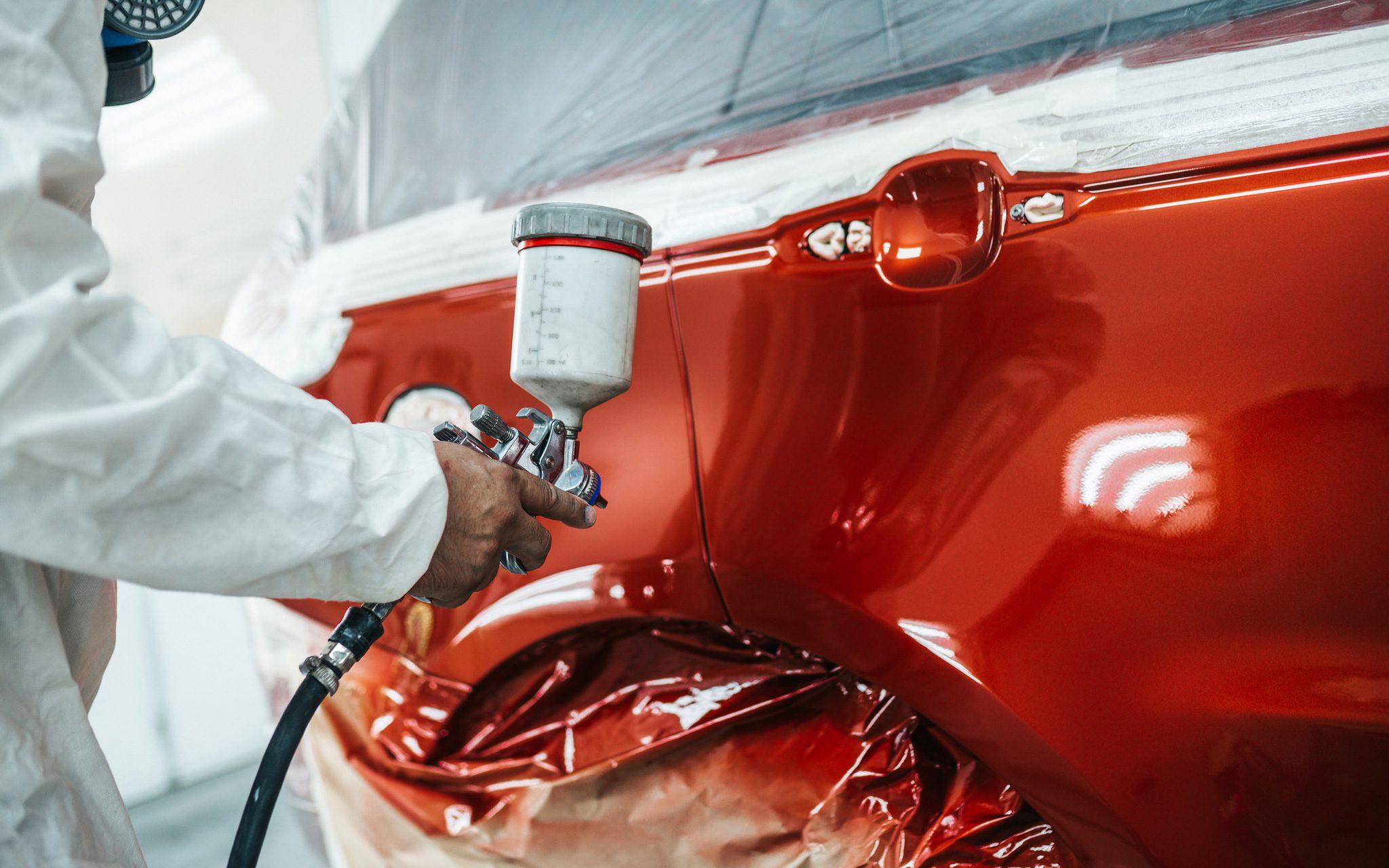 Mann mit Schutzkleidung und Masken lackiert Auto mit Sprühkompressor.