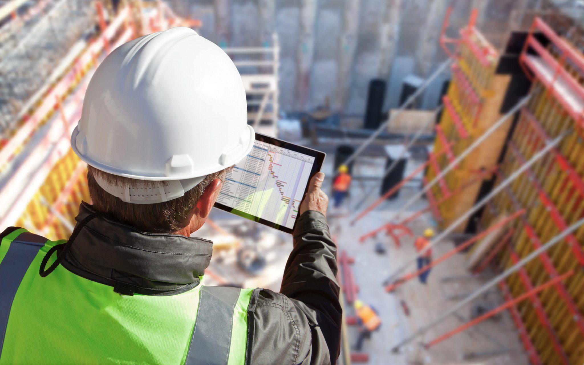 Blick von oben auf die Baustelle mit Ingenieur und Tablet