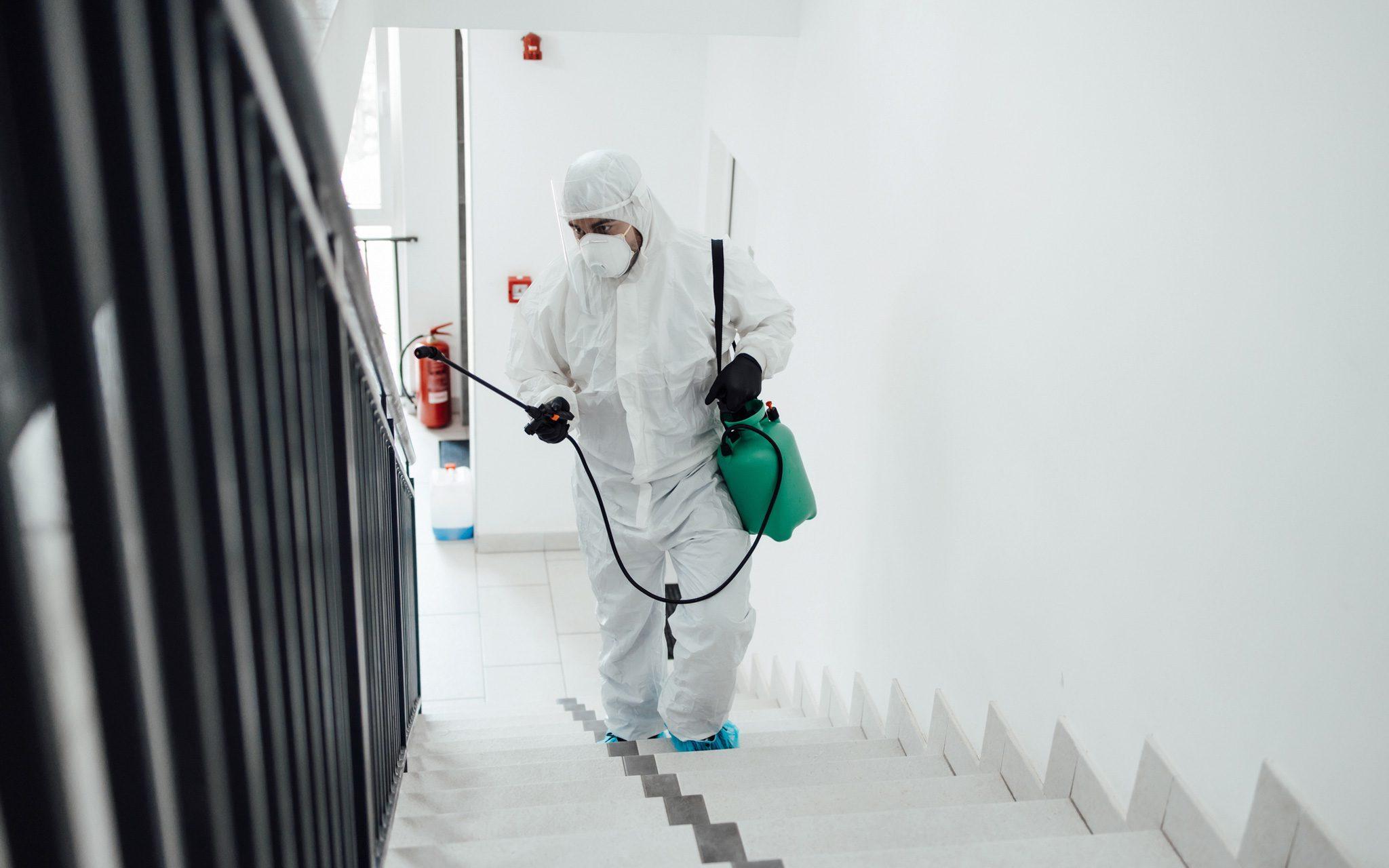 Arbeiter in Arbeitsschutzkleidung, die Virus- und Bakteriendesinfektion im Wohngebäude mit Sprühgerät sprühen.