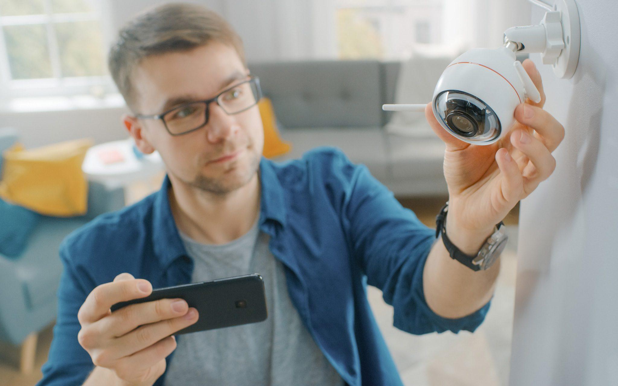 Mann stellt eine moderne Wi-Fi-Überwachungskamera ein