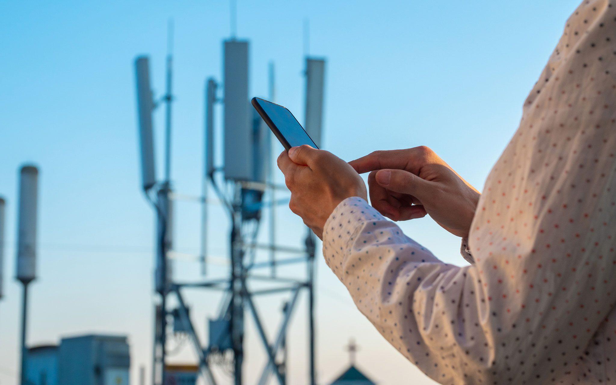 Männer Hand mit Telefon mit 5G Telekommunikationsstation Tower Hintergrund