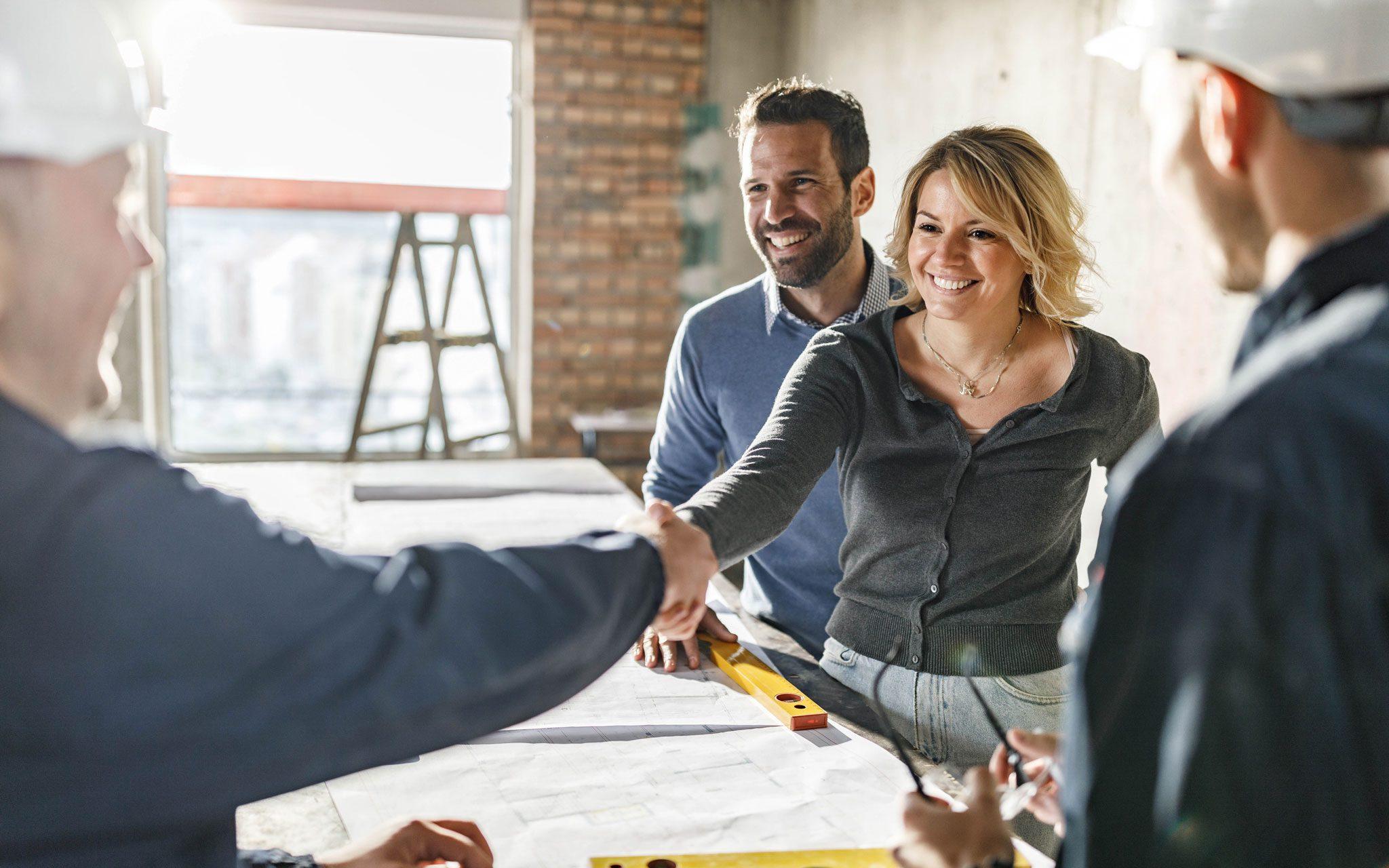 Paar am Planungstisch mit Mitarbeitern der Haus-Bau-Firma