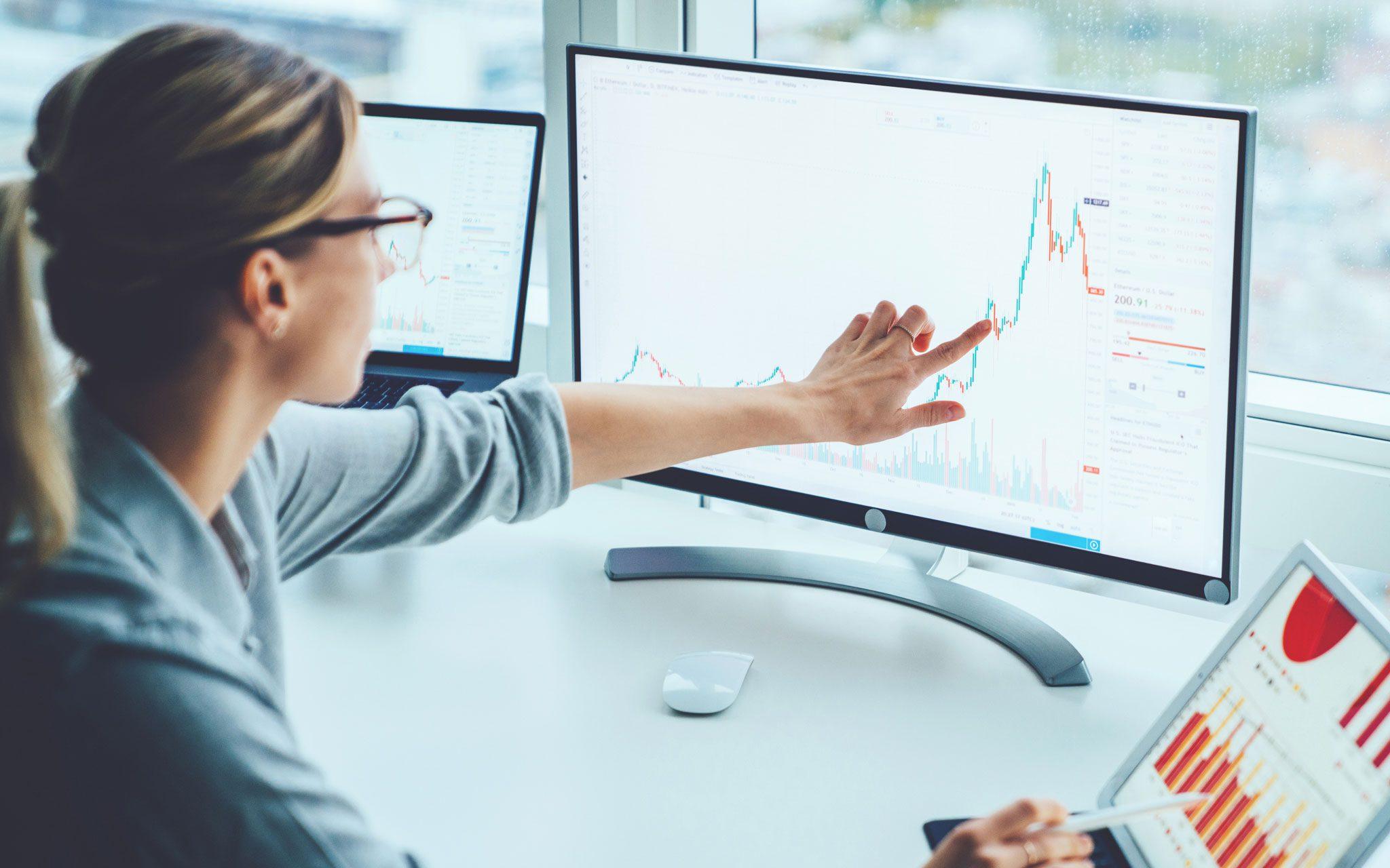 Finanz-Angestellte am Bildschirm mit Börsendaten
