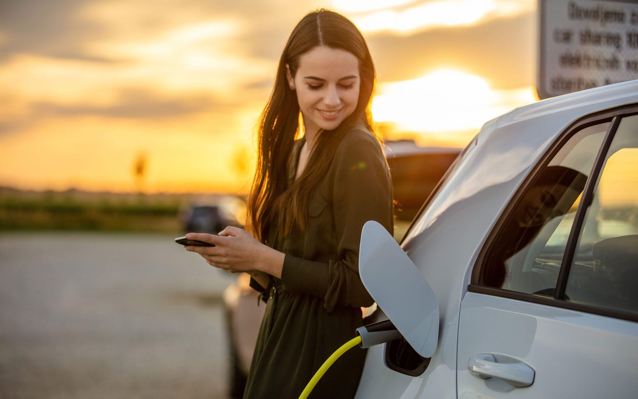 Elektromobilität Ladestation, Frau wartet auf Ladezustand
